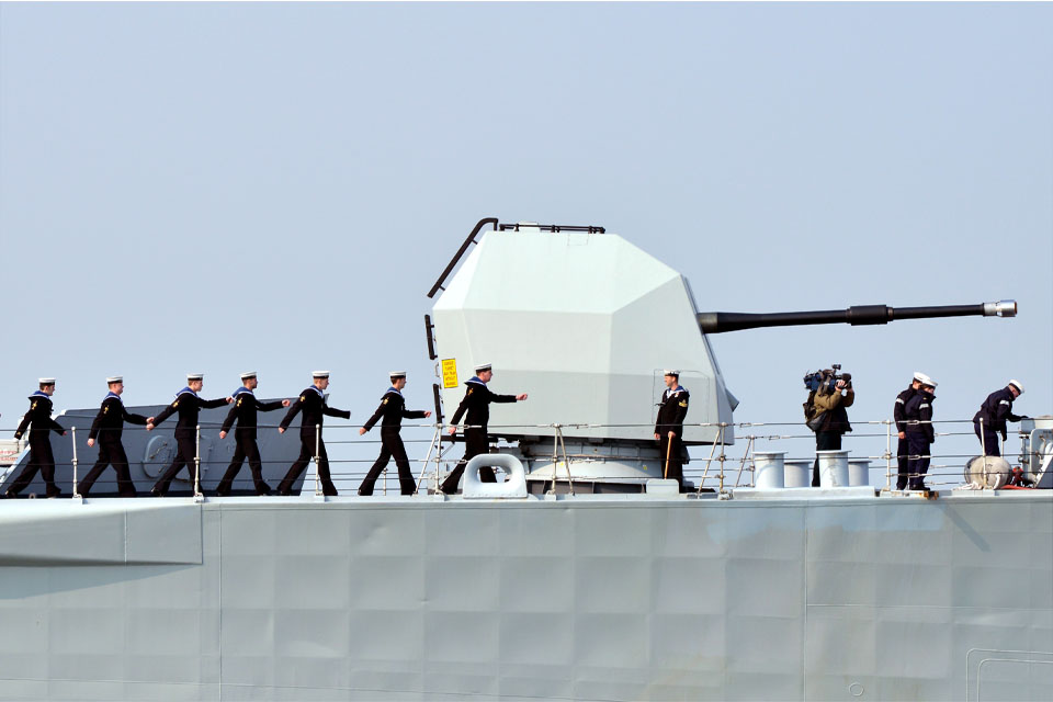 Members of the ship's company march past HMS Edinburgh's 4.5-inch gun
