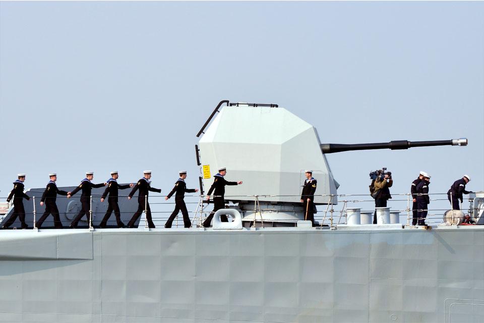 Members of the ship's company march past HMS Edinburgh's 4.5-inch gun