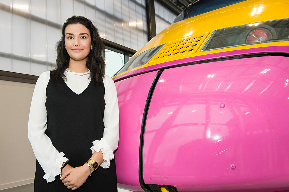 Clara stood next to a train at the National college for High Speed Rail.
