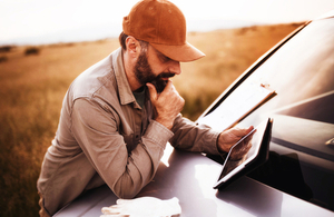 An image of a man leaning against a car bonnet and holding a tablet.