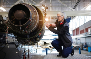 An engineer working on a aircraft turbine.