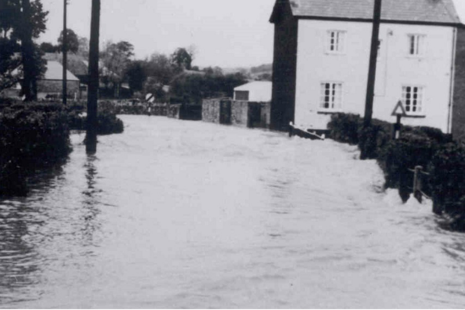 Black and white photograph of flood water flowing through Colyton in 1968