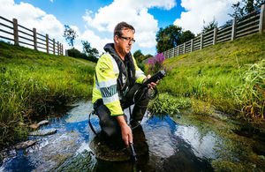 Environment Agency officer in Hi-via jacket using monitoring equipment in a stream