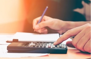 photograph of someone doing calculations using a calculator and pen and paper