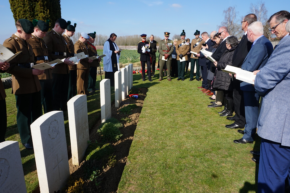 Members of The Royal Irish Regiment and the family of Captain Harvey look on during the rededication service at Noyon New British Cemetery