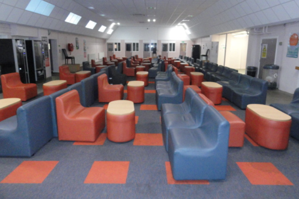 Photograph of Wetherby's open plan visiting hall with comfy seats, carpet and low tables.