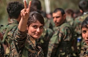 A female fighter of the US-backed Kurdish-led Syrian Democratic Forces (SDF) flashes the victory gesture while celebrating near the Omar oil field in the eastern Syrian Deir Ezzor province on March 23, 2019