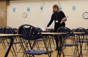 A woman handing out papers in an empty exam hall