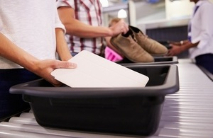 Image of passengers using airport trays