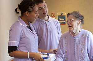 Carers talking to an elderly woman in care home