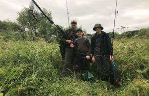 Three anglers standing in tall grass holding their fishing rods and a net