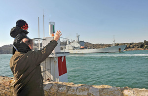 A man carrying a young boy waves from the shore as HMS Scott returns to Plymouth [Picture: Leading Airman (Photographer) Caroline Davies, Crown copyright]