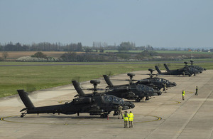 Apache attacked helicopters line up side-by-side on an airfield