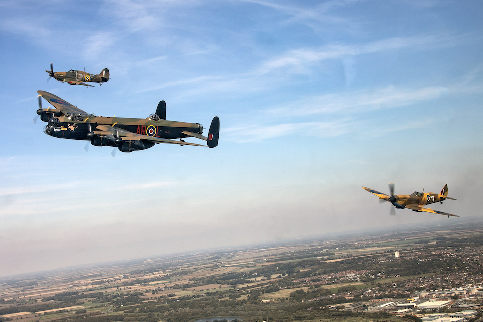 Historic aircraft fly over the countryside