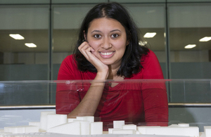 Woman in red top posing in front of 3d model.