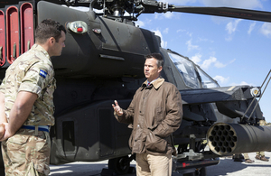 Minister for the Armed Forces Mark Lancaster speaks to a British Army soldier in front of a helicopter