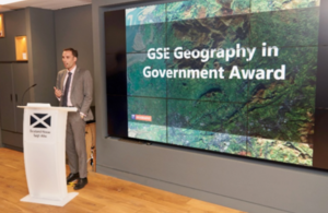 David Wood, GSE Head of Geography, introduces the Geography in Government Awards at Scotland House in London. He is stood behind a podium addressing those in the audience.