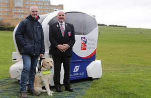Blind veterans Dave Woollett and Alan Walker and guide dog Jasper with a driverless car.