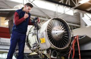 An engineer works on an aircraft turbine.