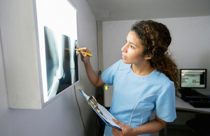A nurse inspects an X-ray scan.