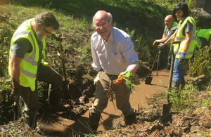 Lord Gardiner with volunteers digging out American skunk cabbage from a drainage channel in Kent