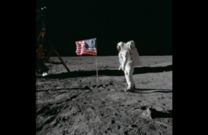 Astronaut on the moon next to the American flag