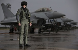 Typhoon pilot in current aircrew equipment assemblies (AEA) stood in front of a row of Typhoon Aircraft with wet pan and some form of water tower in background