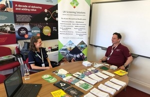 Occupational health technician, surrounded by informative leaflets, speaks to a member of LLWR workforce