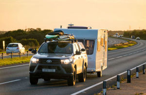 Car towing a caravan at sunset
