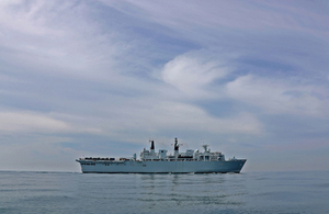 HMS Albion, a British warship, sails alone on a quiet sea with a wide open sky in the background