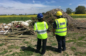 EA and HMRC officers stand in front of a pile of waste on an illegally operating site