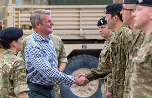 Image of Defence Minister Stuart Andrew meeting service personnel at Jellalabad barracks in front of a Mastiff armoured vehicle