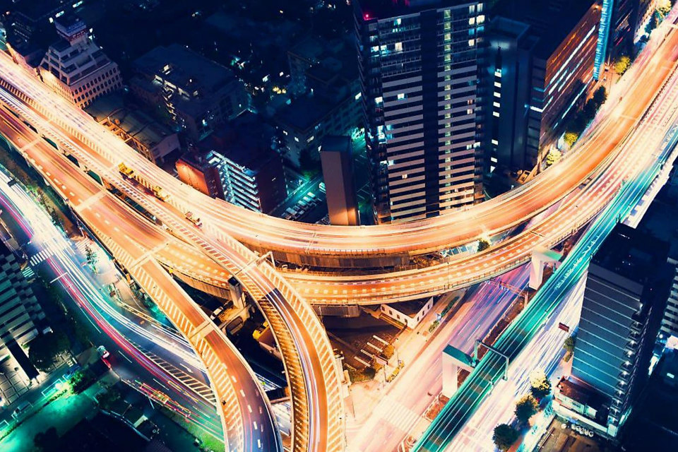Aerial view of a highway intersection at night in Shinjuku, Tokyo. (Credit: TierneyMJ/Shutterstock)