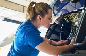 A female engineer works on a plane turbine.