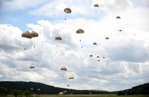 Paratroopers parachute through the sky