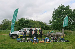 Four Environment Agency fisheries officers standing in from of an Environment Agency vehicle and trailer with equipment such as aerators on the ground in front of them