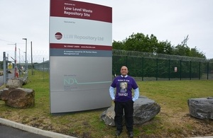 John Maxwell standing in front of the LLWR totem