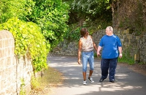 Carer walking with a man with Down's sydrome