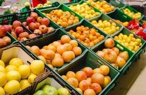 A supermarket shelf stocked with fruit produce