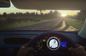 Computer generated imagery of the view from the driver's seat of a car, showing a road ahead, with a car travelling towards the driver