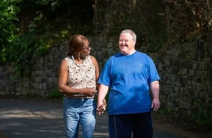 Carer walking with a man with Down's syndrome walking down the street