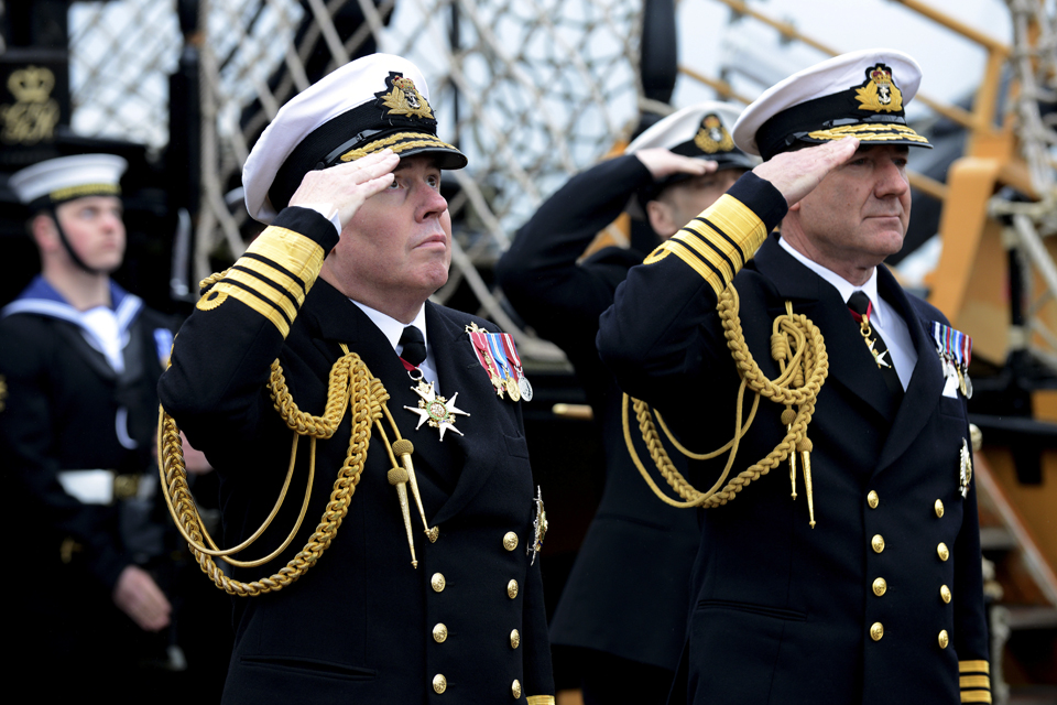Admiral Stanhope and Admiral Zambellas salute as the Cross of St George flag is lowered