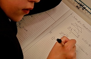 Close-up of child writing in maths workbook