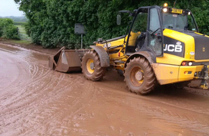 A digger removing mud washed on to the road
