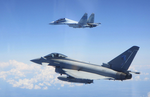 An RAF Typhoon jet flies alongside a Russian fighter jet against a bright blue sky