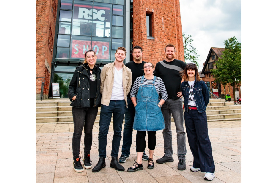 Six digital theatre fellows standing in front of the Royal Shakespeare Company building in Stratford