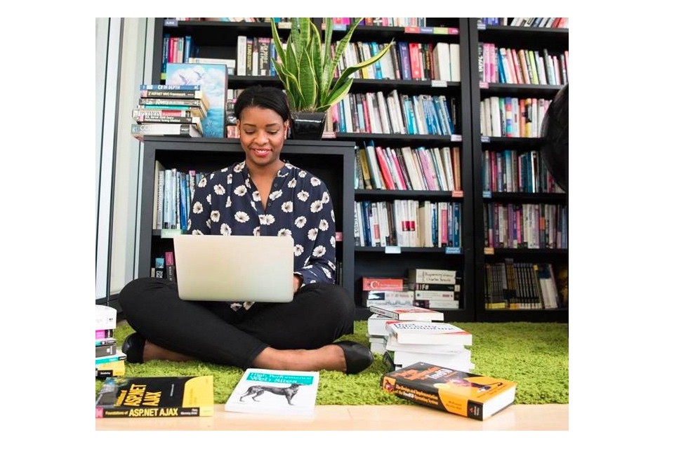 Woman sitting on the floor of a library using a laptop surrounded by books