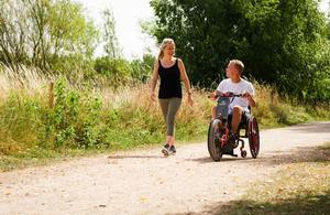 A woman walks besides a man in a wheelchair.
