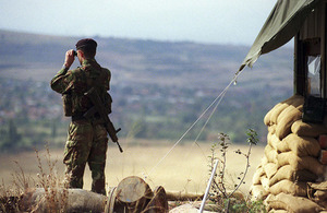 A sentry watches through a pair of binoculars in Kosovo