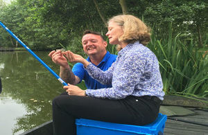 EA Chair Emma Howard Boyd sitting beside water holding a fishing rod during an angling coaching session with Carl Nye, Project Manager for Get Hooked on Fishing
